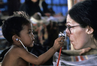 Earning trust - a doctor allows her young refugee patient to examine her. Thailand - Cambodian border.