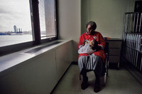 A foster grandparent feeding an HIV infected infant in the hospital. New York