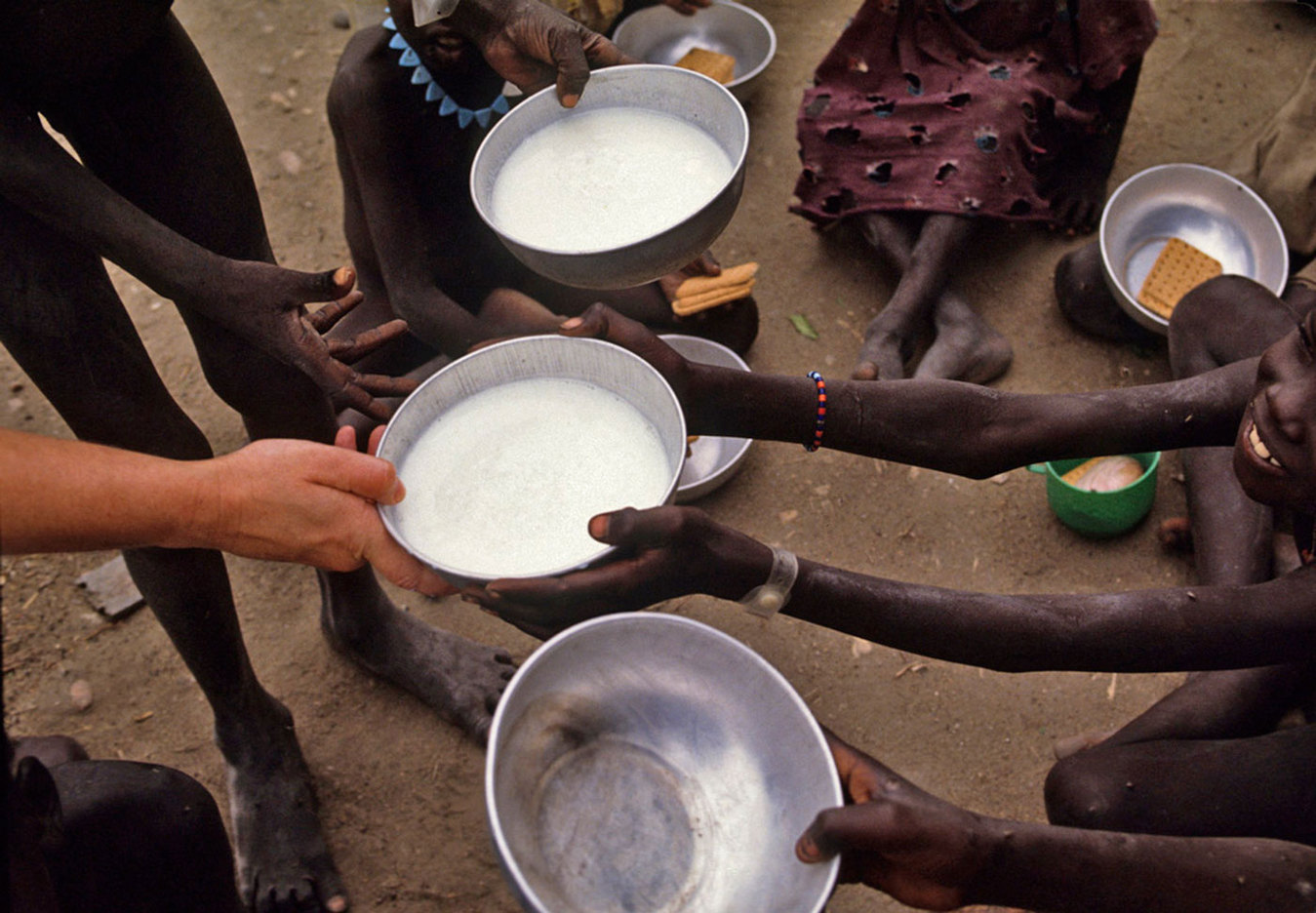 Distributing milk to children in a food distribution center in Southern Sudan : CRISIS : Viviane Moos |  Documentary Photographer