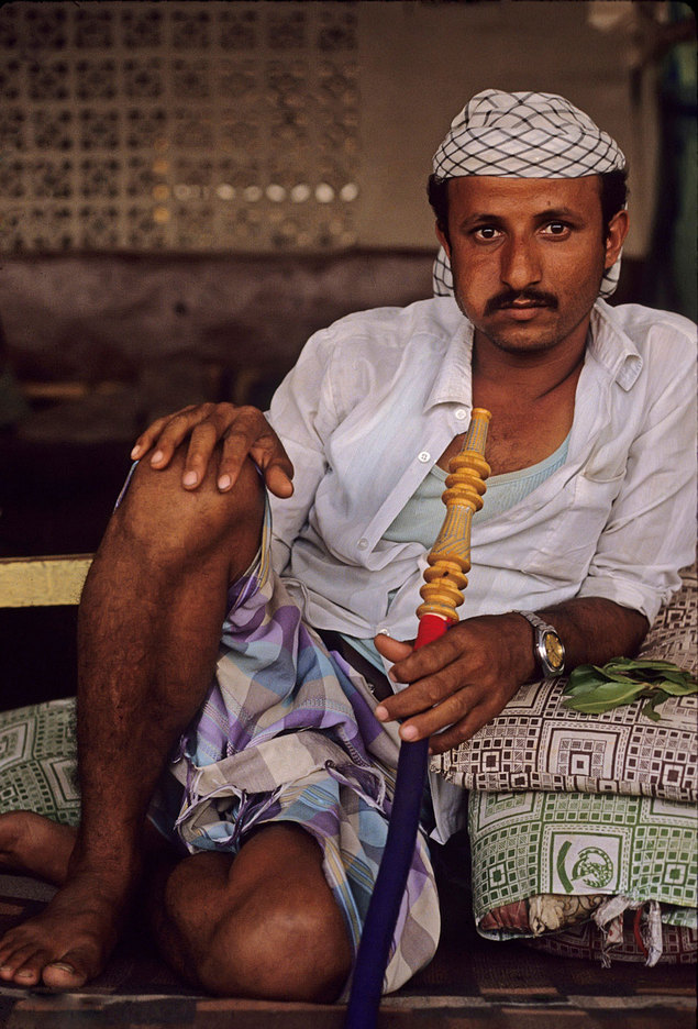 A cafe patron smoking a water-pipe and chewing khat, Yemen : PORTRAITS : Viviane Moos |  Documentary Photographer