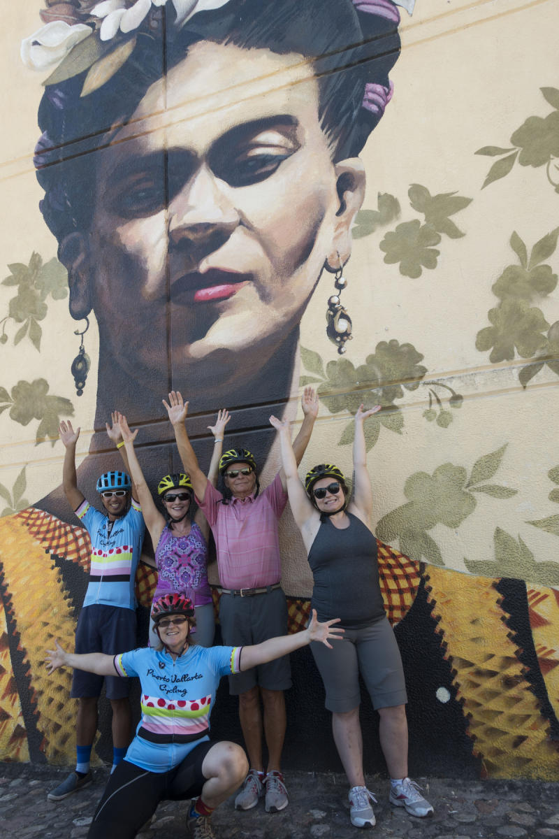 Participants and  owners of the Fat Bike Graffiti and Art Tour posing in front of a  three story high mural of Frida Kahlo. : PUERTO VALLARTA - Wall Art & Bicycle Tour : Viviane Moos |  Documentary Photographer