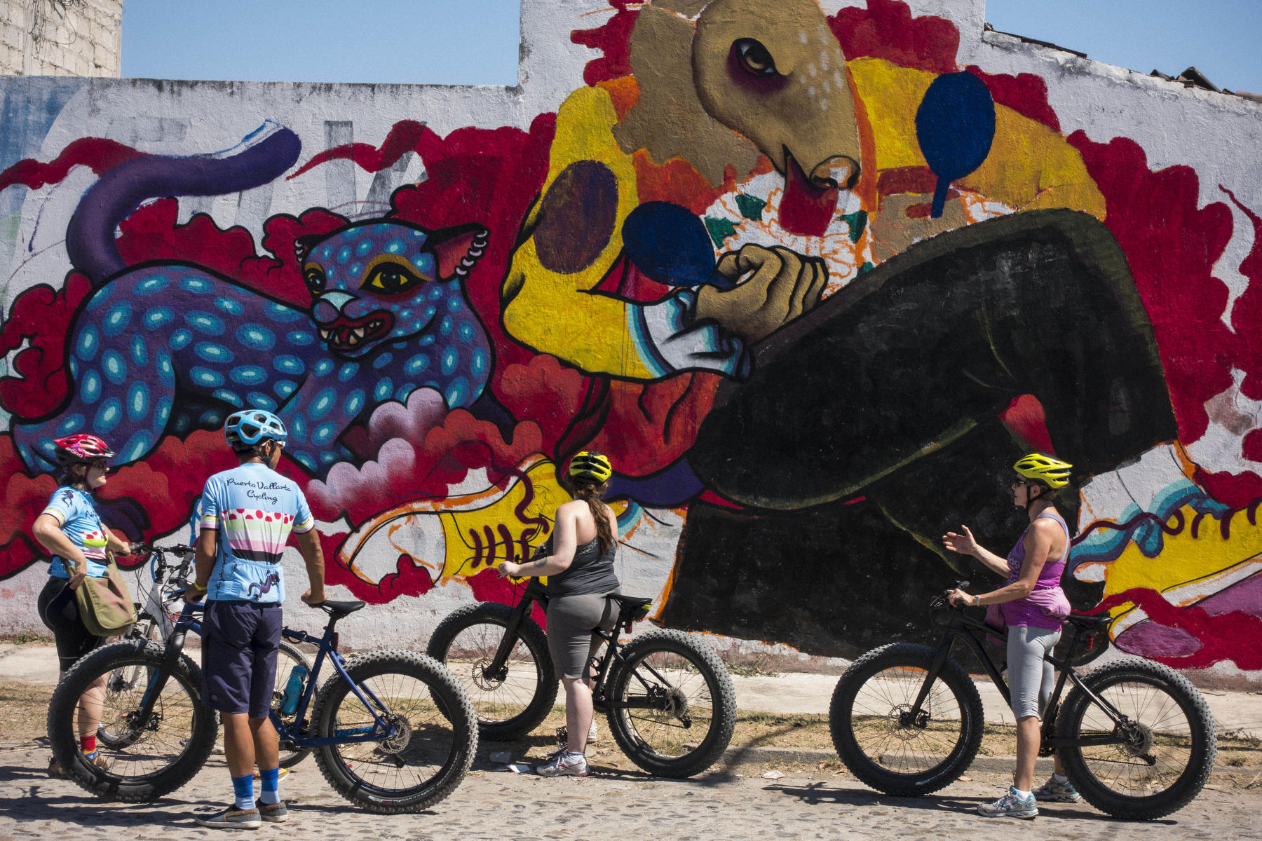 Participants and the owners of Puerto Vallarta Cycling  in front of a work in progress mural : PUERTO VALLARTA - Wall Art & Bicycle Tour : Viviane Moos |  Documentary Photographer