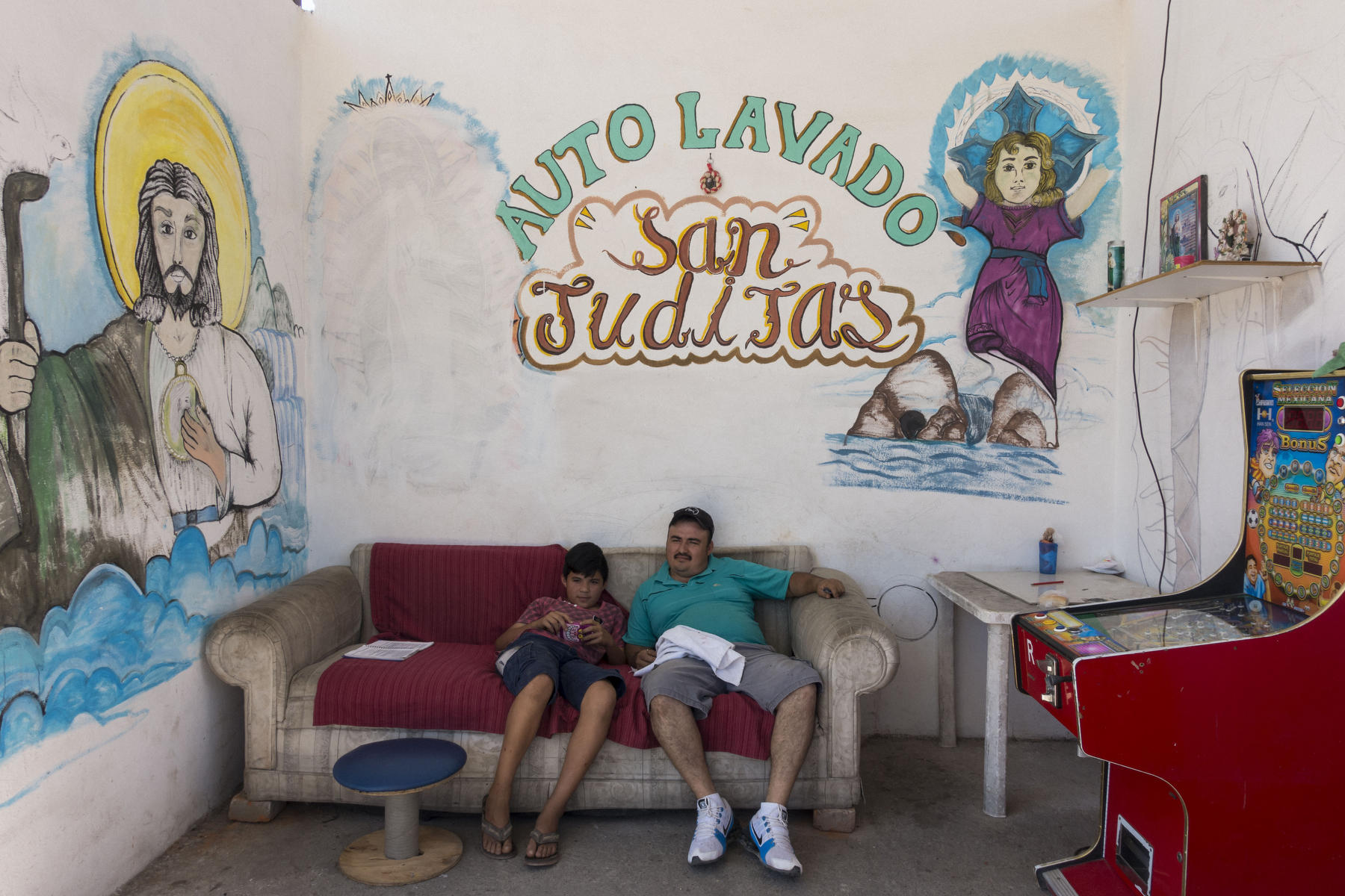 A father and son resting on sofa surrounded by religious murals at a car-wash.