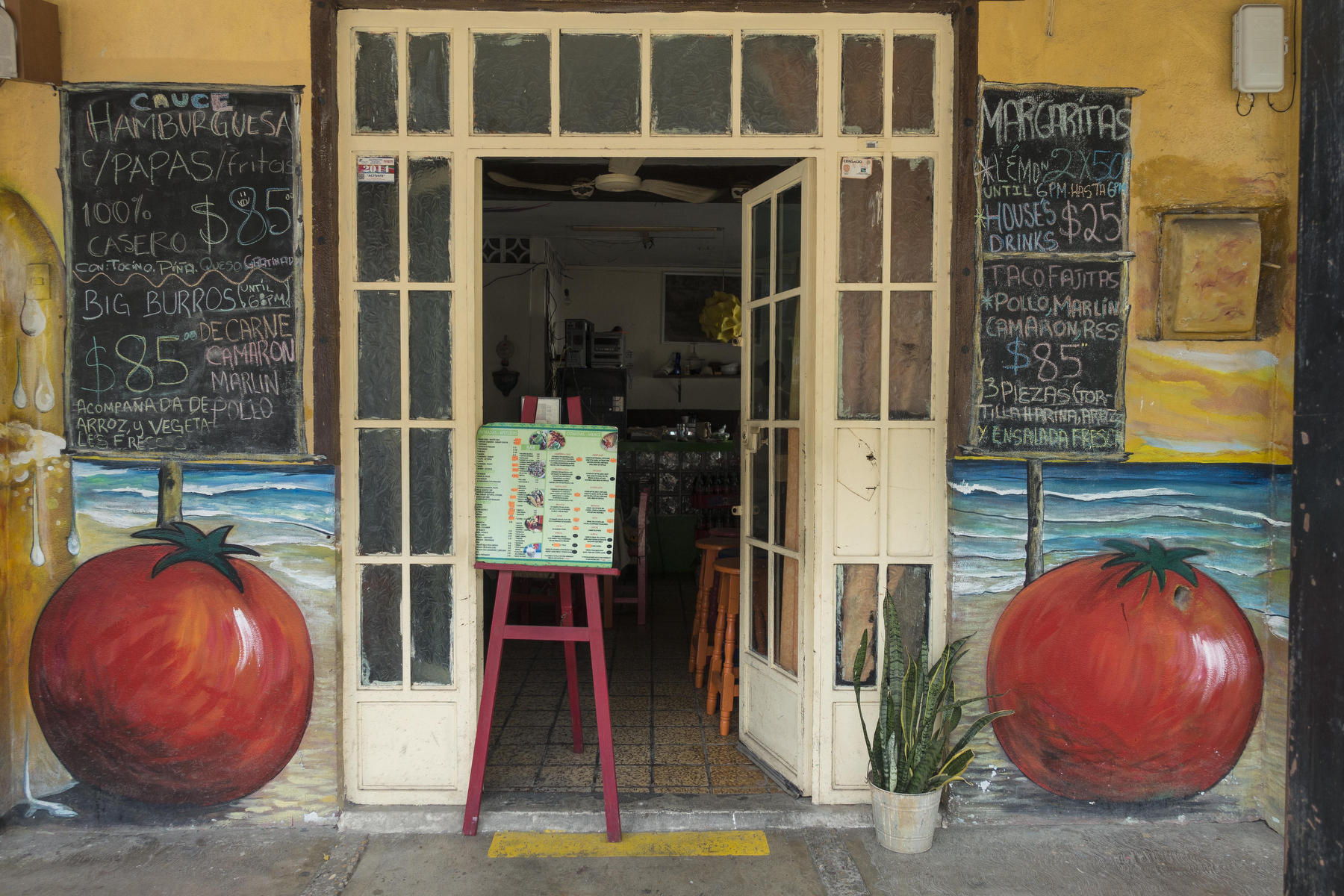 Cauce restaurant in Old Town features giant painted tomatoes on each side of the entrance door. : PUERTO VALLARTA - Wall Art & Bicycle Tour : Viviane Moos |  Documentary Photographer